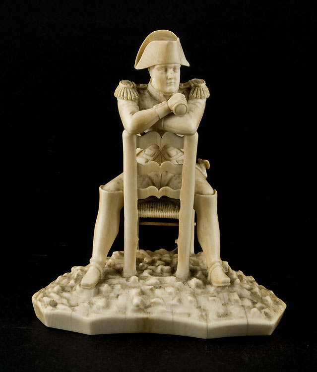 Antique ivory statuette of Napoleon Bonaparte sitting astride a chair.
