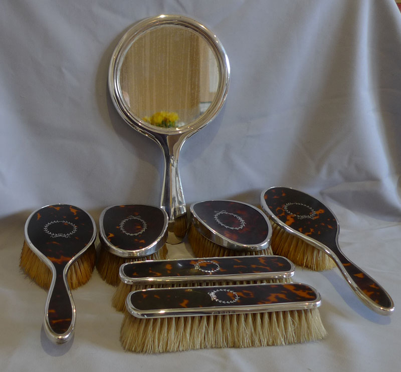Harlequin set of tortoiseshell, silver piquer and silver brushes and mirror.