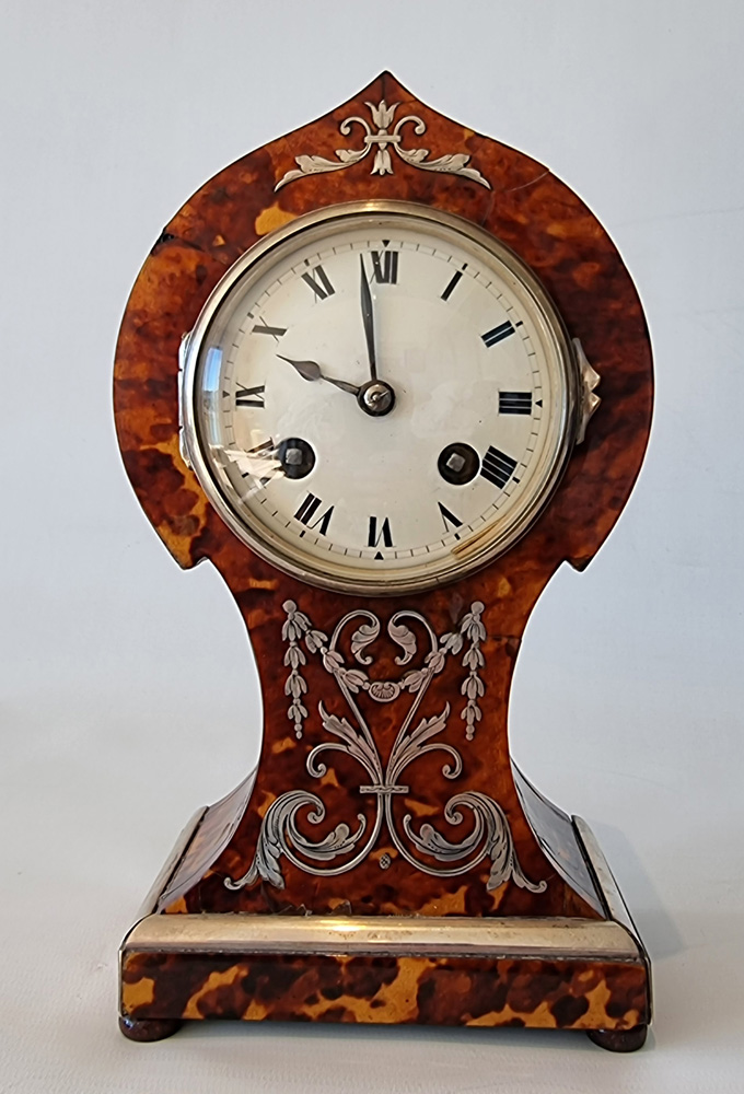 Antique tortoiseshell mantel clock with silver inlay and stringing and ivory feet.