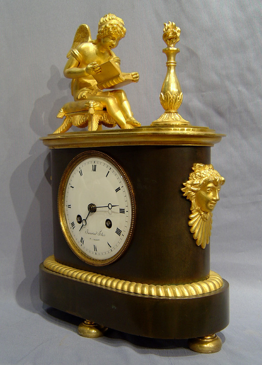 Antique French Empire patinated bronze and ormolu clock of boot shape of Cupid studying.