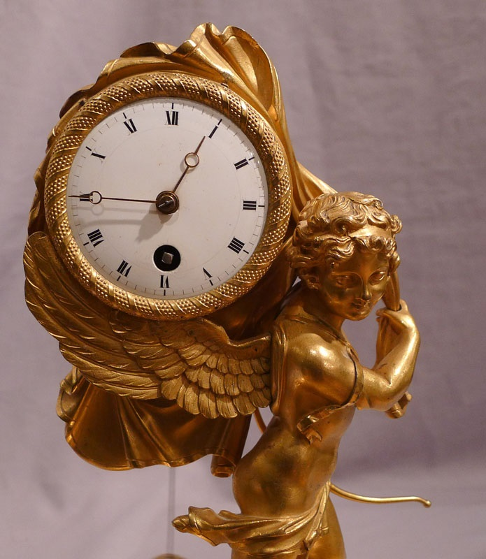 Antique French Empire miniature mantel clock of Cupid carrying time.