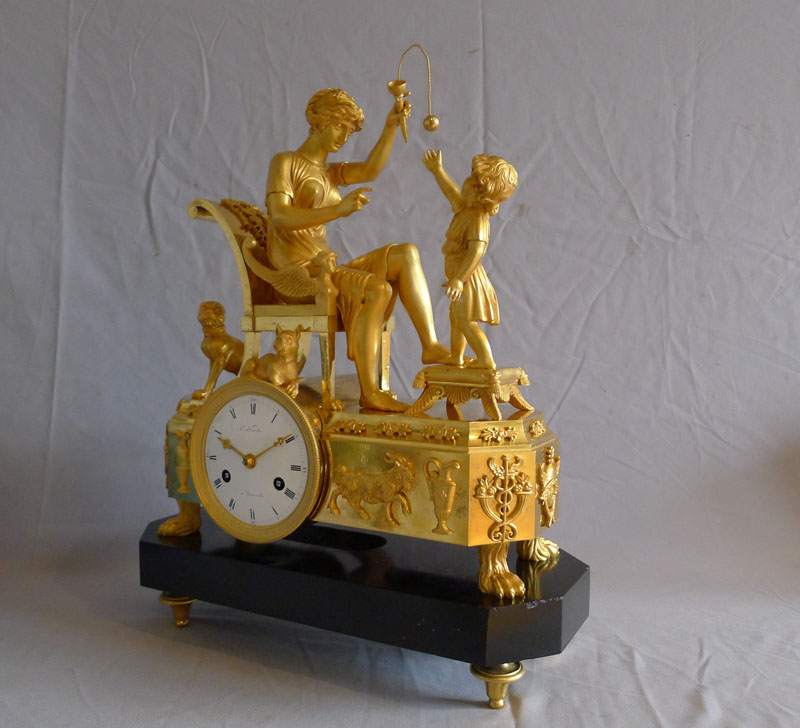 Fine French Empire clock of woman playing with child in ormolu and black marble.