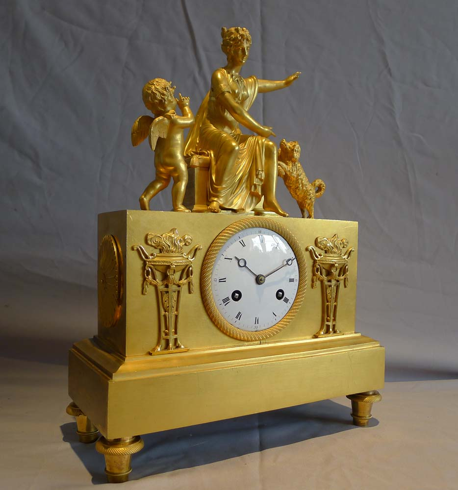 Antique ormolu French Empire mantel clock of woman playing with dog.