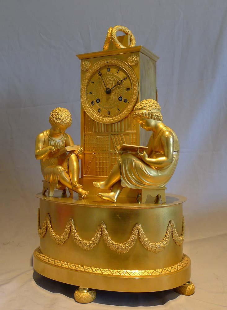 Antique French Empire ormolu library clock of two children reading before a book case