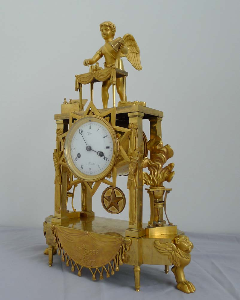 Fine and rare French Empire clock of Cupid as Magician uncovering flaming hearts with 3 cup trick.