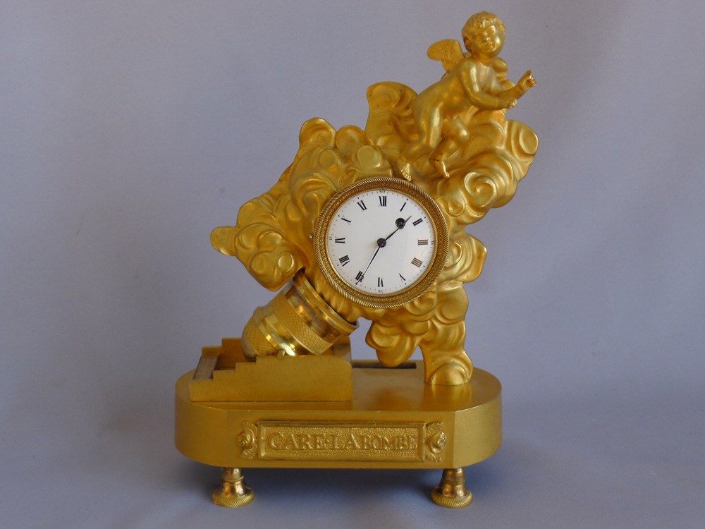 Antique French Empire ormolu miniature clock of Cupid being fired from a motar.