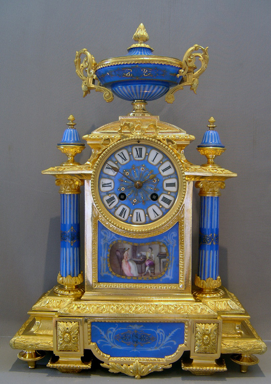 French antique clock set in porcelain and ormolu with silver highlights.