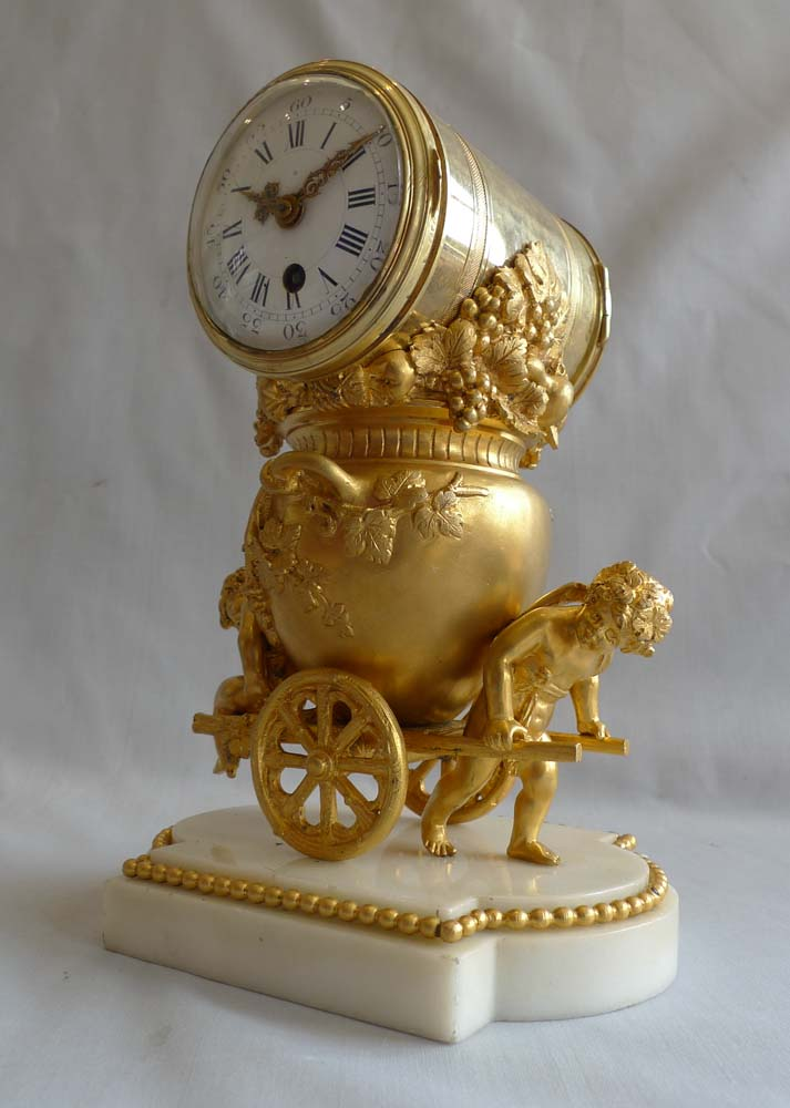 Antique French ormolu clock of two cupids pulling a cart carrying an urn full of grapes.