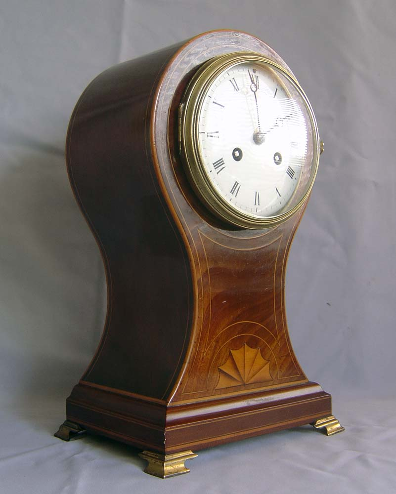 Antique Edwardian mantel clock of balloon form veneered in mahogany with satinwood stringing