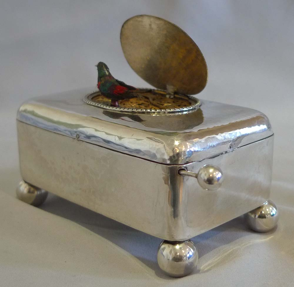 Antique singing bird box in hammered silver case.