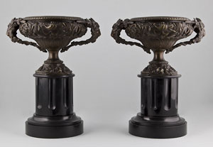 Pair of late Victorian bronze vases on black marble columns.