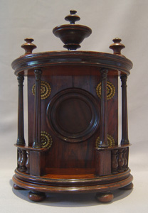 Watch stand in rosewood in bow fronted bronze mounted case with columns and finials.