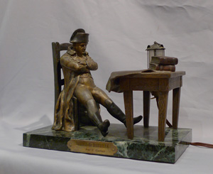 Antique Napoleon Bonaparte figural lamp showing Napoleon seated at a table.