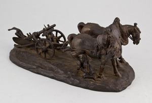Antique bronze of working horses with plough, tended by groom.