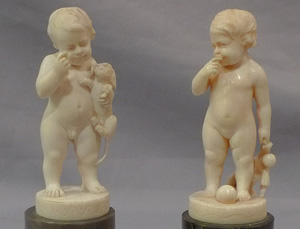 Pair of antique ivory statuettes of children.