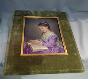 Porcelain plaque of young girl knitting in velvet and ormolu frame.