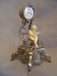 Antique Austrian silver gilt and ivory miniature clock of cupid in a bower.