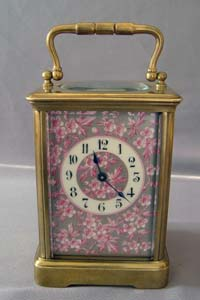 Antique porcelain panelled French carriage clock with apple blossom decoration.
