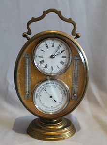 Antique French gilt bronze oval combination desk timepiece with aneroid barometer and thermometers.
