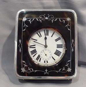 Tortoiseshell and silver piquet strut clock with 8 day goliath clockwatch.