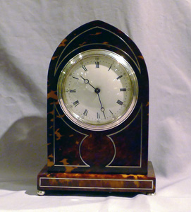 Fine Tortoiseshell mantel clock lancet topped with silver stringing and enamel dial.