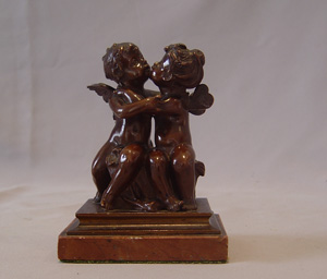 Antique French romantic bronze of winged puttae kissing set on a marble base.