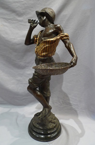 Good sculpture of a black boy smoking a pipe and holding a basket.