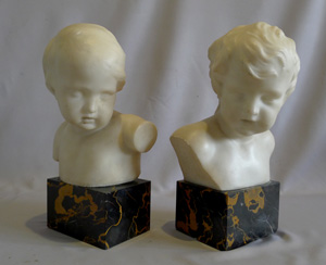 Antique pair of white marble busts of children on variegated marble bases.