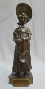 Antique bronze of a young woman in 19th century dress signed P. Kowalczewski.