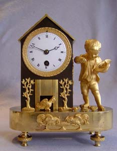 Antique French Empire genre clock of boy feeding chickens.