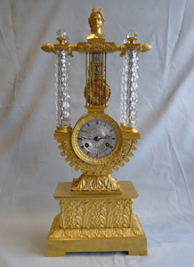 Rare antique mantel clock in crystal and ormolu, Charles X period with remote pendulum.