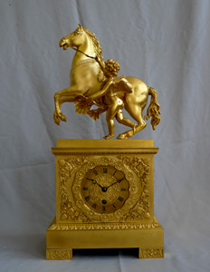 Antique French Empire mantel clock in ormolu of Cupid holding a horse.