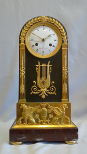 French Empire antique mantel clock in ormolu, patinated bronze and marble signed Mesnil.