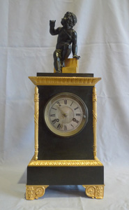 Antique Charles X mantel clock in patinated bronze and ormolu.