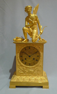 Antique French ormolu mantel clock of Charles X period of a kneeling Cupid.
