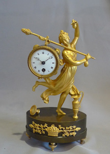 Antique French Empire miniature mantel clock of a dancing baccante in ormolu and patinated bronze.