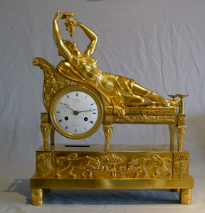 Antique French Empire clock of a Bacchante lying on her day bed.