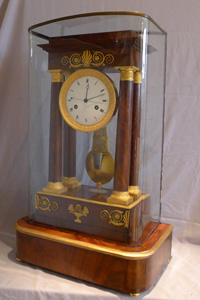 Antique French Empire period, flame mahogany and ormolu mounted musical portico clock.