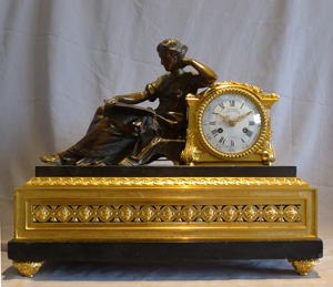 Antique French mantel clock in ormolu, black marble and patinated bronze of woman reading.