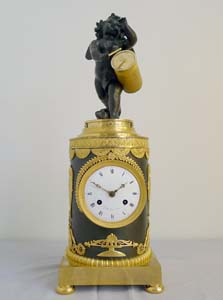 Antique French Ist Empire clock in patinated bronze and ormolu of cupid playing a drum.