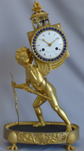 Antique Empire ormolu mantel clock of Amor carrying a laterna magika signed Z. Raingo, Tournay