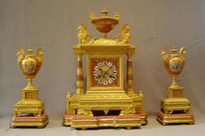 Egyptian revival coral porcelain and ormolu three piece clock set.