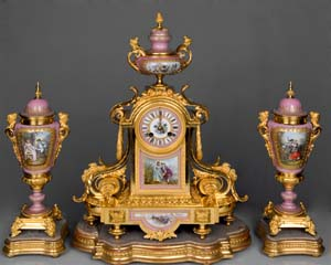 French antique clock set in pink jewelled porcelain and ormolu with silver highlights.