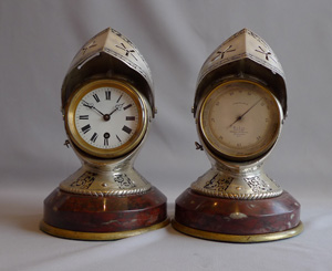 Antique desk clock and barometer in form of silvered and engraved medieval helmets with visors.