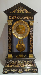 Antique ebonized portico clock inlaid with brass and shell.
