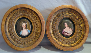 Pair porcelain hand painted oval plaques in oval giltwood frames.