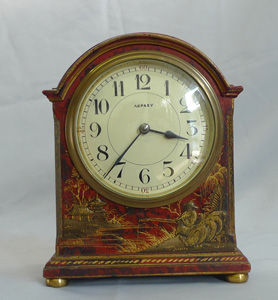 Antique Asprey chinnoiserie mantel clock in red lacquer.