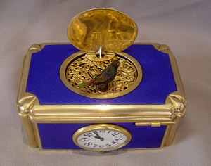 Swiss singing bird box in electric blue guilloche enamel with watch to front.