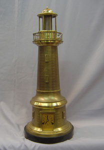 Antique automaton industrial clock in form of lighthouse with rotating light.
