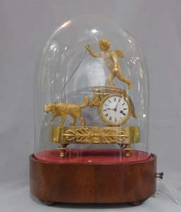 French Empire antique miniature musical mantel clock of dog pulling a chariot.